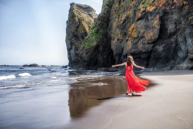 Mooie energieke jonge vrouw die vrij op het strand loopt