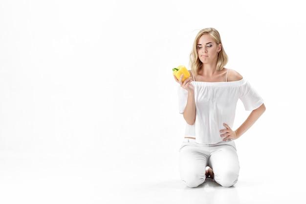Mooie ernstige blonde vrouw in een witte blouse kijkt naar de gele paprika. gezond eten en dieet
