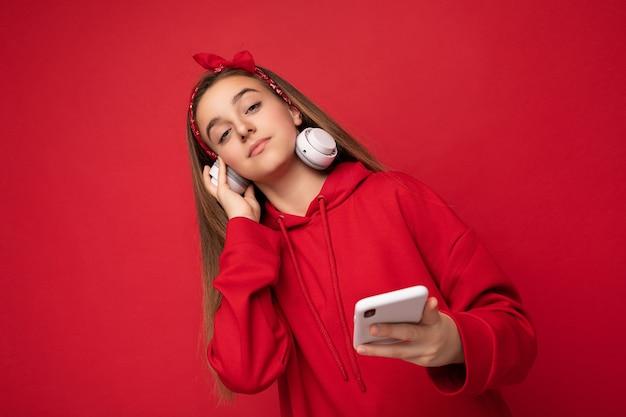 Mooie ernstige brunette meisje dragen rode hoodie geïsoleerd op rood oppervlak houden en gebruiken smartphone dragen witte draadloze koptelefoon luisteren naar coole muziek kijken naar camera