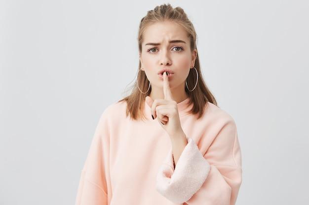 Mooie ernstige jonge vrouw met blond haar gekleed in roze sweatshirt en ronde earings die vinger bij lippen houden die vragen om geen lawaai te maken en privé vertrouwelijke informatie te verbergen. zeer geheim