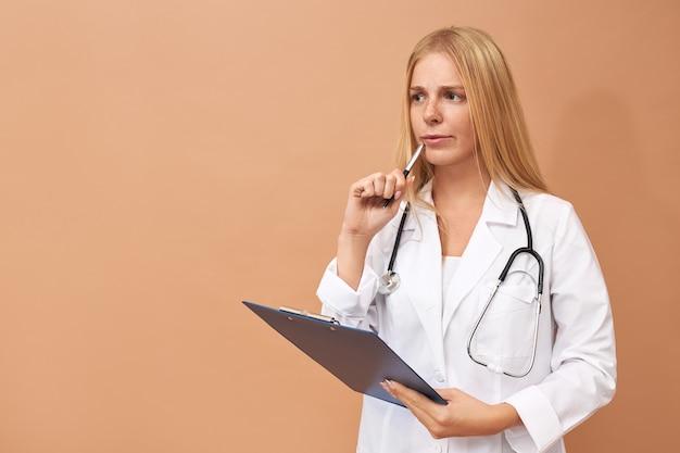 Mooie ervaren jonge vrouwelijke beoefenaar in witte chirurgische jas denken