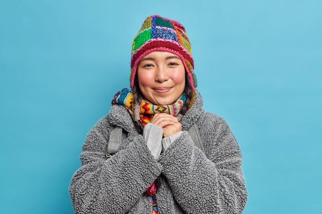 Mooie eskimo-vrouw met roze wangen houdt handen bij elkaar en lacht aangenaam gekleed in mode warme muts en winterjas woont op arctische plaats of noordpool
