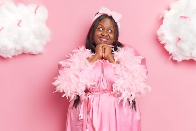 Mooie etnische donkere gevilde dame houdt handen onder kin glimlacht aangenaam en kijkt opzij draagt badjas heeft aangename dromen geïsoleerd op roze