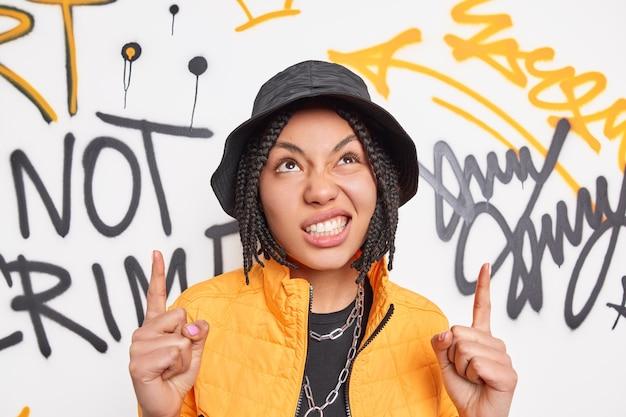 Mooie etnische hipster meisje met brutale uitdrukking klemt tanden punten hierboven toont iets tegen graffiti muur gekleed in modieuze outfit