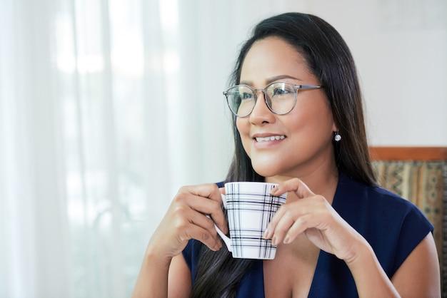 Mooie etnische zakenvrouw met mok koffie