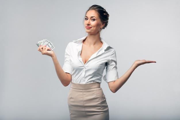 Mooie europese bedrijfsvrouw die in bureaukleren dollars houdt