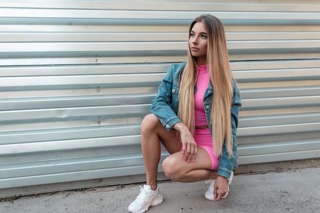 Mooie europese jonge blonde vrouw in een blauw denim jasje in trendy roze korte broek in een roze top in stijlvolle witte sneakers zit in de buurt van een metalen wand op een straat op een zomerdag. leuk meisje vormt buiten