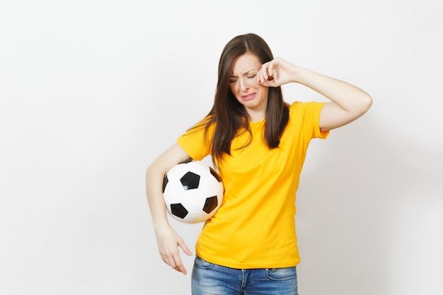 Mooie europese jonge boos huilende vrouw, voetbalfan of speler in gele uniform houden voetbal geïsoleerd op een witte achtergrond. sport, voetbal, gezondheid, gezond levensstijlconcept.