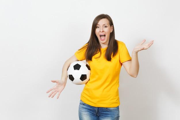 Mooie europese jonge boos schreeuwende vrouw, voetbalfan of speler in gele uniform houden voetbal geïsoleerd op een witte achtergrond. sport, voetbal, gezondheid, gezond levensstijlconcept.