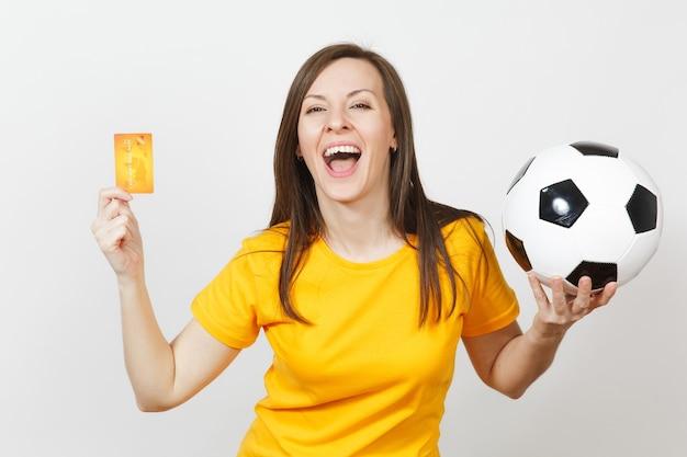 Mooie europese jonge vrolijke vrouw, voetbalfan of speler in geel uniform met creditcard voetbal geïsoleerd op een witte achtergrond. sport, voetbalspel, opwinding lifestyle concept.