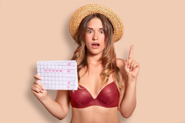 Mooie europese jonge vrouw heeft een verbaasde uitdrukking, steekt wijsvinger, gekleed in rode bikini en strooien hoed