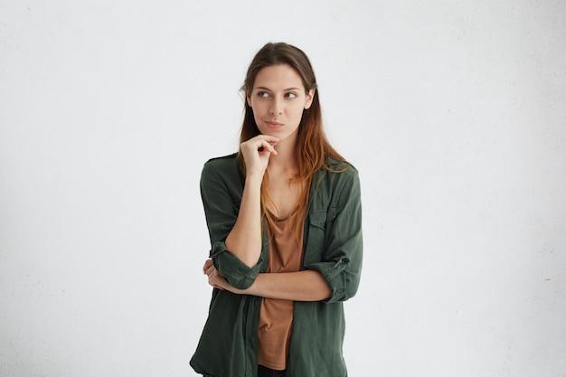 Mooie europese vrouw die met lang donker haar hand op kin houdt peinzend opzij kijkt om idee in haar hoofd te krijgen.