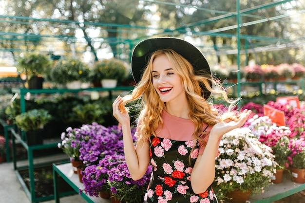 Mooie europese vrouw die van goede dag geniet. blij blinde vrouw met plezier op de oranjerie met bloemen.