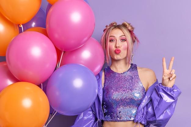 Mooie europese vrouw houdt lippen gevouwen maakt vredesgebaar speciale gelegenheid poses met veelkleurige helium ballonnen viert