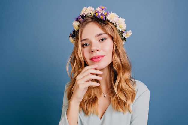 Mooie europese vrouw met bleke huid poseren op donkerblauwe muur
