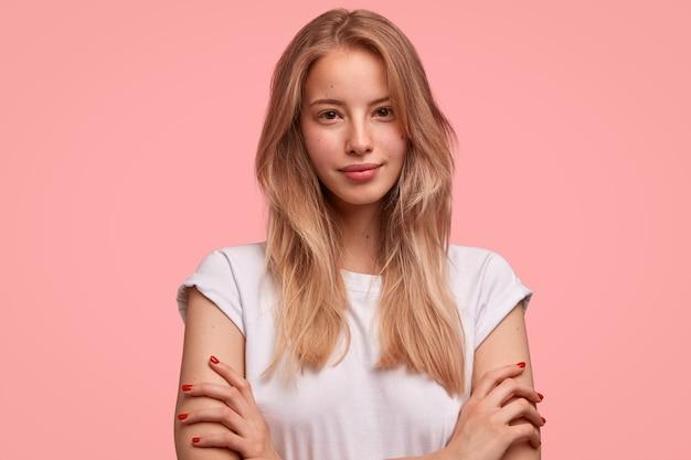 Mooie europese vrouw met steil haar, houdt de handen gekruist, draagt een casual wit t-shirt, staat tegen een roze muur