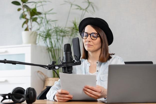 Mooie europese vrouw podcaster met koptelefoon en microfoon neemt podcast op in opname
