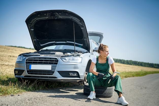 Mooie europese vrouw repareert de auto op de weg