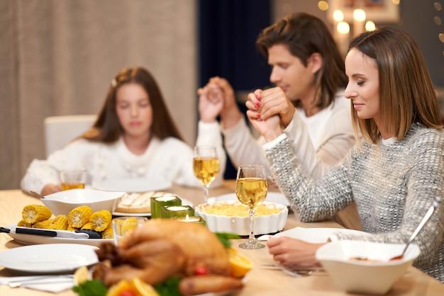 Mooie familie die bidt tijdens het vakantiediner?