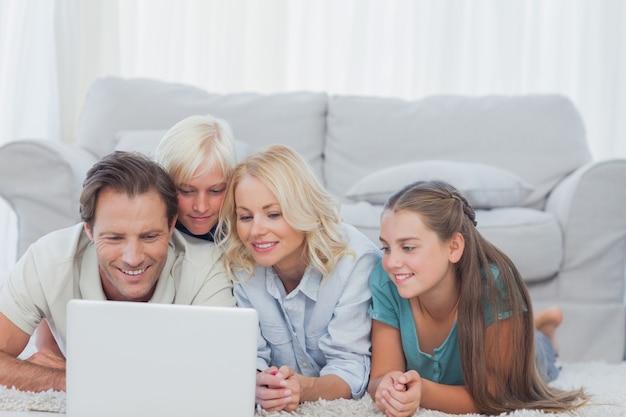 Mooie familie die laptop met behulp van die op een tapijt ligt