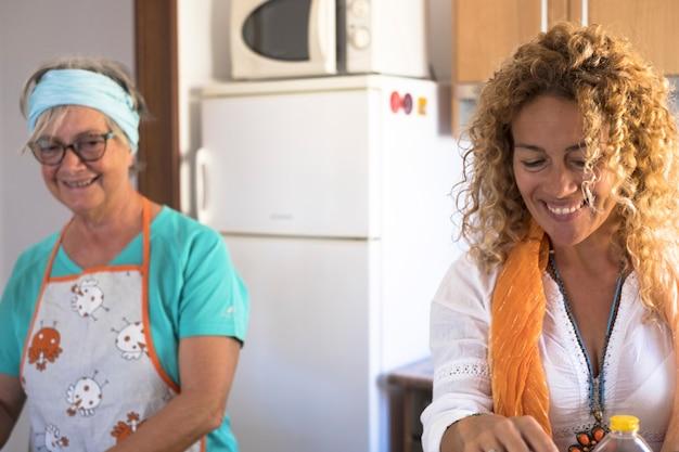 Mooie familie thuis koken en samen plezier hebben - oma die laat zien hoe je coockies en vis kookt - indoor lifestyle - blanke vrouw en volwassen vrouw genieten - blank