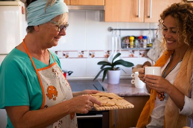 Mooie familie thuis koken en samen plezier hebben - oma die laat zien hoe je coockies en vis kookt - indoor lifestyle - blanke vrouw en volwassen vrouw genieten