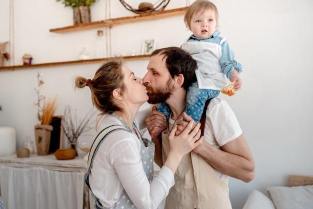 Mooie familie van moeder, vader en baby bereidt deeg en knuffelen in de keuken