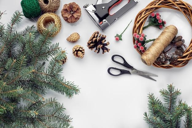 Mooie feestelijke handgemaakte krans basis met drie bultjes in de buurt van draden en twijgen blauwe kerstboom...