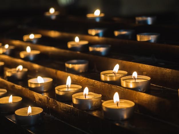 Mooie, feestelijke kaarsen in de duisternis van de oude kerk