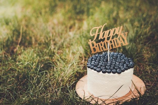 Mooie feestelijke kwarktaart voor kinderen met bosbessen met de inscriptie happy birthday.