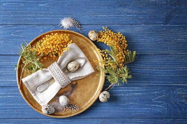 Mooie feestelijke paastafel met mimosa en kwarteleitjes
