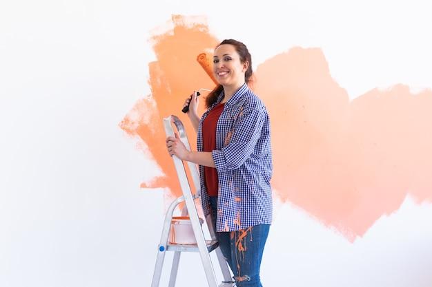 Mooie feman die de muur met verfroller schildert. portret van een jonge mooie vrouw schilderij