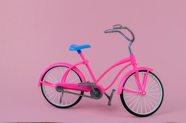 Mooie fiets met blauw zadel op roze achtergrond.