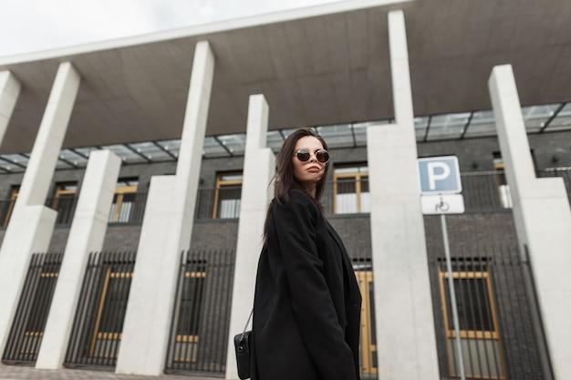 Mooie fijne jonge vrouw in trendy zonnebril in mooie zwarte jeugdblazer met stijlvolle handtas loopt in de buurt van modern gebouw in de stad. mooi mooi stedelijk meisje in mode vrijetijdskleding op straat.