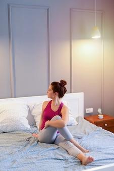 Mooie fit middelbare leeftijd vrouw die zich uitstrekt vroeg in de ochtend in haar hoofd.