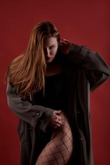 Mooie fit slanke vrouw met verleidelijke make-up in zwarte sexy lingerie en zwarte regenjas