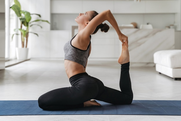 Mooie fit vrouw doen stretching oefening op vloer thuis, yoga beoefenen