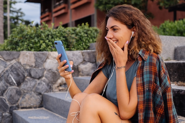 Mooie fit vrouw in korte broek, geruite overhemd zitten op de trap bij zonsondergang licht smartphone houden