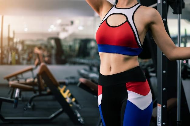 Mooie fit vrouw in sportschool met apparatuur interieur