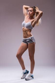 Mooie fit vrouw met perfect lichaam geïsoleerd op een grijze achtergrond