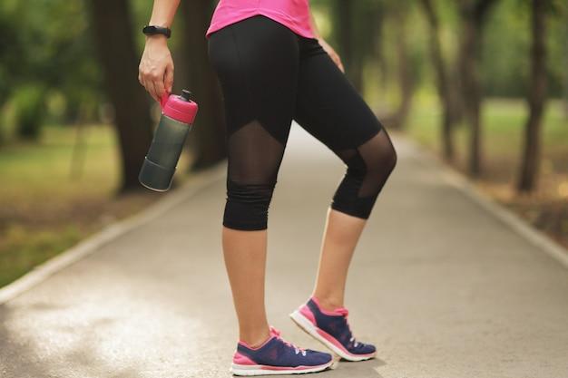 Mooie fitness atleet runner vrouw drinkwater in het park