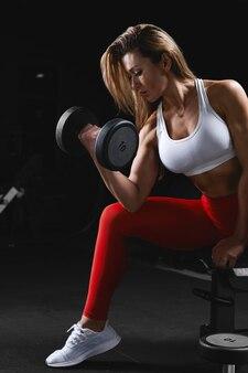 Mooie fitness model oefeningen doen en verschillende camera's poseren in de sportschool in de sportschool