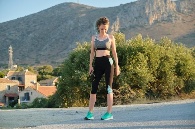 Mooie fitness runner meisje met behulp van smartphone en koptelefoon luisteren muziek. actieve gezonde levensstijl bij adolescenten achtergrond zonnige zomerdag in de bergen