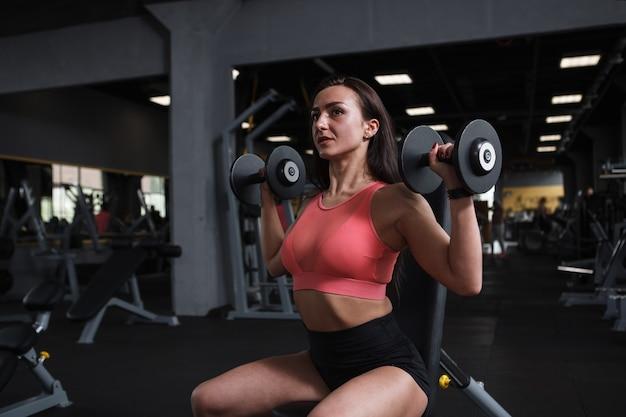 Mooie fitness vrouw doet schouders oefening met halters in sportstudio