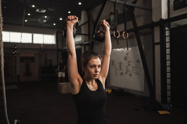 Mooie fitness vrouw kettlebells op te heffen, trainen in de sportschool