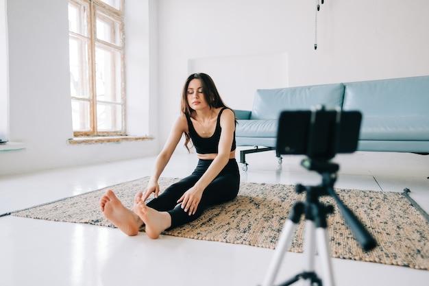Mooie fitness vrouw maken rekoefeningen voor camera op statief binnenshuis thuis
