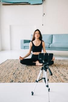 Mooie fitness vrouw mediteren voor camera op statief, thuis yoga doen