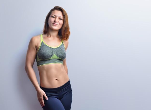 Mooie fitness vrouw met buikspieren in een grijze top zwarte legging geïsoleerd op een studio achtergrond.