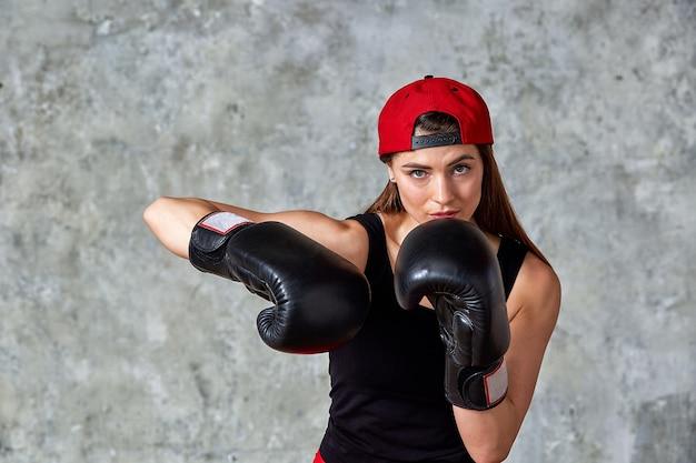 Mooie fitness vrouw poseren in zwarte bokshandschoenen