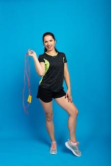 Mooie fitness vrouw springt het touw, studio-opname